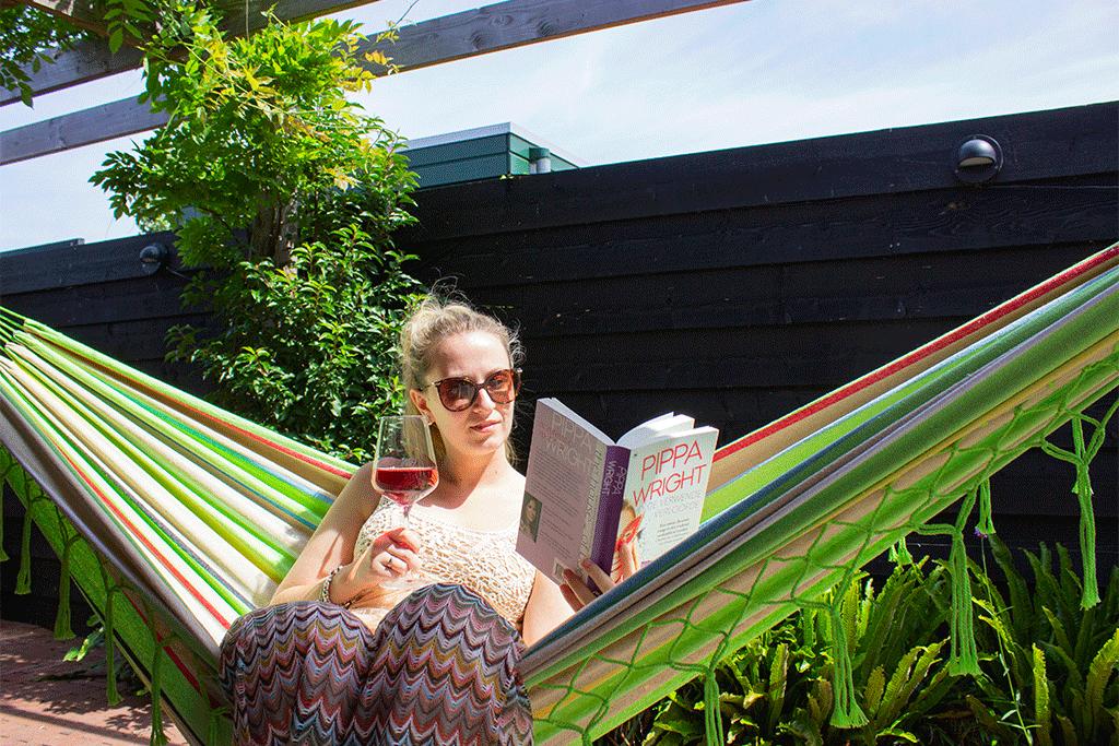 vrouw leest boek in groene hangmat met franjes