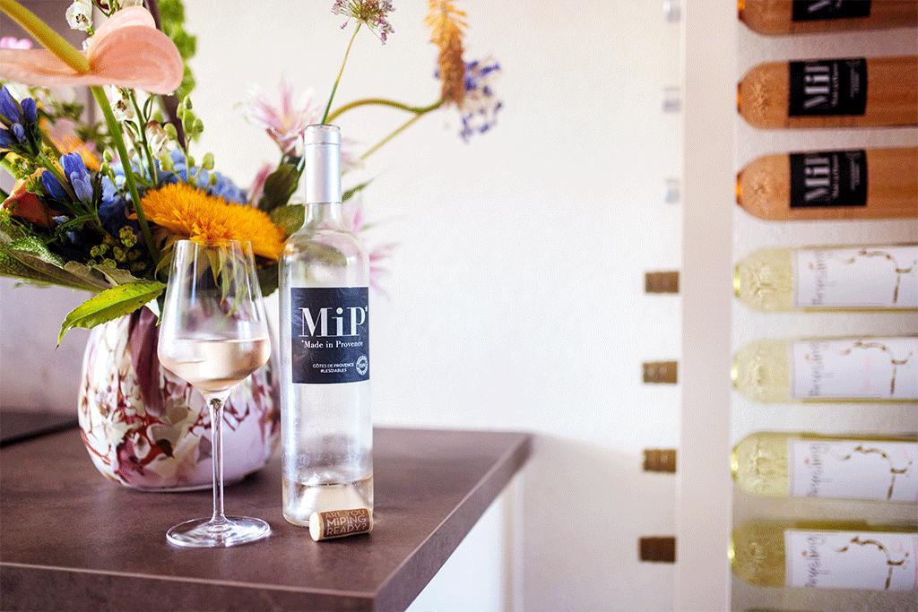 Wijnfles met wijnglas op keukenblad naast wijnpaal